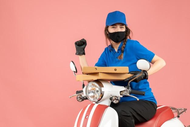 Vooraanzicht van een jonge, gelukkig lachende vrouwelijke koerier met een medisch masker en handschoenen die op een scooter zitten en bestellingen afleveren op een pastelkleurige perzikachtergrond