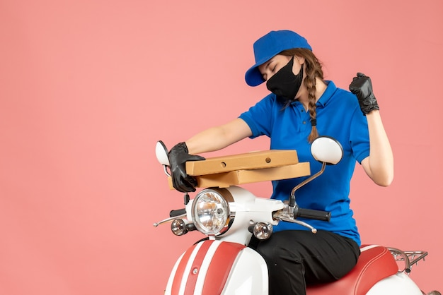 Vooraanzicht van een jonge, gelukkige emotionele vrouwelijke koerier met een medisch masker en handschoenen die op een scooter zitten en bestellingen afleveren op een pastelkleurige perzikachtergrond
