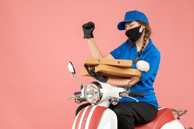Vooraanzicht van een jonge, gelukkige vrouwelijke koerier met een medisch masker en handschoenen die op een scooter zitten en bestellingen afleveren op een pastelkleurige perzikachtergrond