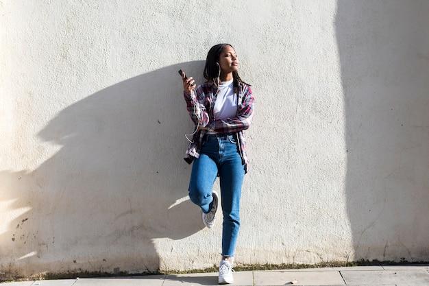 Vooraanzicht van een jonge glimlachende afrikaanse amerikaanse vrouw die zich in openlucht terwijl het glimlachen en het luisteren muziek door oortelefoons in een zonnige dag bevinden