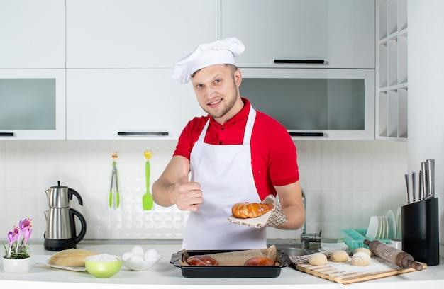 Vooraanzicht van een jonge glimlachende mannelijke chef-kok die een houder draagt die een van de versgebakken gebakjes vasthoudt en een goed gebaar maakt in de witte keuken