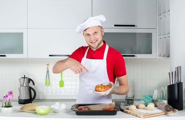 Vooraanzicht van een jonge glimlachende mannelijke chef-kok met een houder die een van vers gebakken gebakjes in de witte keuken vasthoudt en wijst