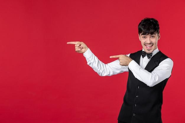 Vooraanzicht van een jonge lachende mannelijke ober in een uniform met vlinderdas op de nek en naar boven gericht aan de rechterkant met beide handen op de rode muur
