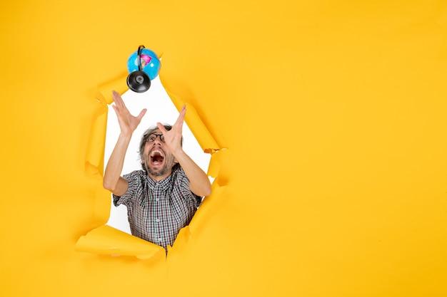 Vooraanzicht van een jonge man die de aardbol op de gele muur gooit en vangt