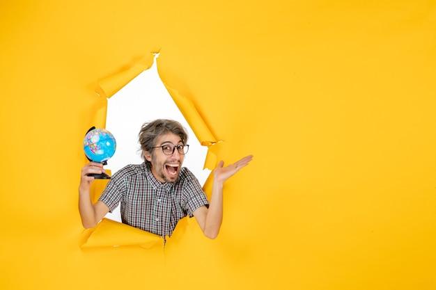 Vooraanzicht van een jonge man die een aardbol op een gele muur houdt