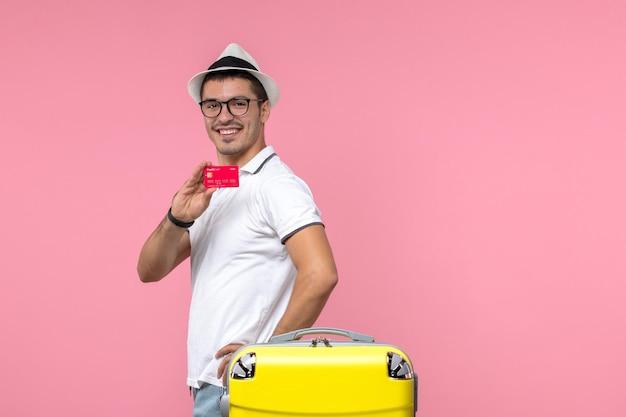 Vooraanzicht van een jonge man die een bankkaart vasthoudt en lacht op de roze muur
