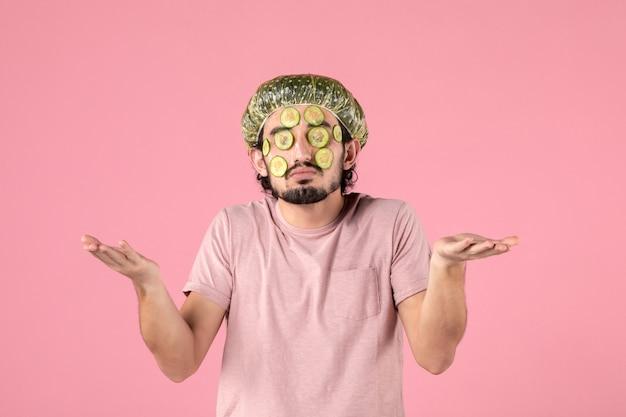 Vooraanzicht van een jonge man die een komkommermasker op zijn gezicht op een roze muur aanbrengt