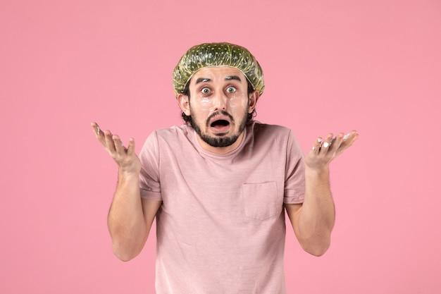 Vooraanzicht van een jonge man die een masker op zijn gezicht op een roze muur aanbrengt