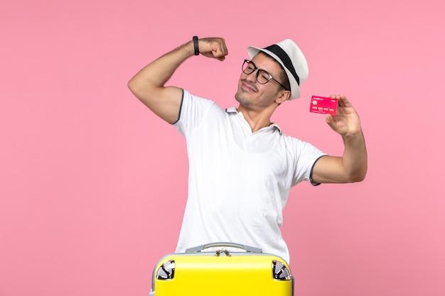 Vooraanzicht van een jonge man die emotioneel een bankkaart vasthoudt op vakantie op een lichtroze muur