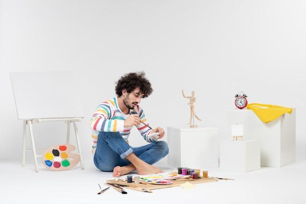 Vooraanzicht van een jonge man die foto's maakt met verf op een witte muur