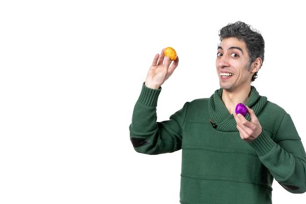 Vooraanzicht van een jonge man die gekleurde beschilderde eieren vasthoudt en probeert het tegen elkaar te slaan op een witte muur