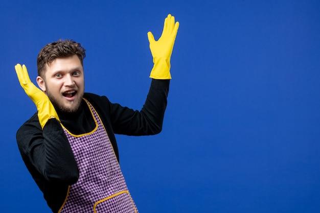 Vooraanzicht van een jonge man die handen opent die op een blauwe muur staan