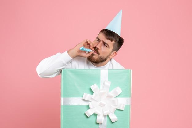 Vooraanzicht van een jonge man die in de huidige doos op een roze muur staat
