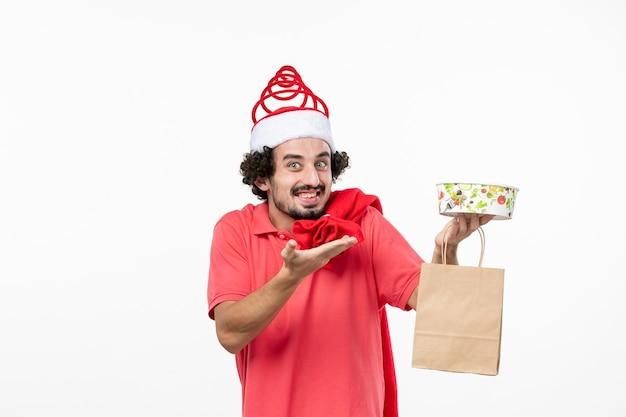 Vooraanzicht van een jonge man die lacht met bezorgmaaltijden op een witte muur