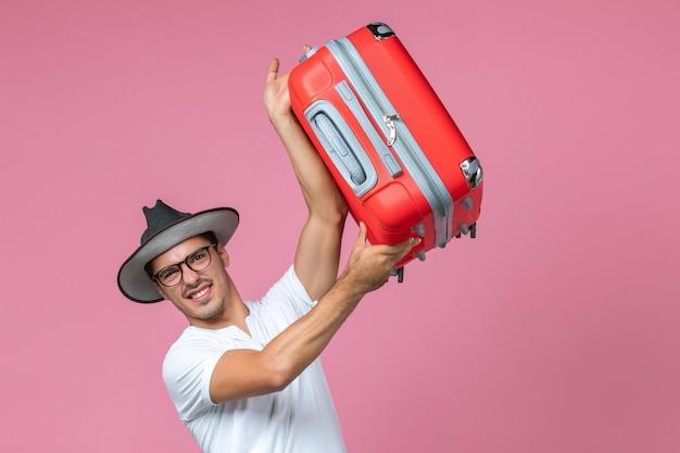 Vooraanzicht van een jonge man die op vakantie gaat en een rode tas op de roze muur houdt