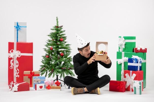 Vooraanzicht van een jonge man die rond vakantie zit presenteert boomspeelgoed op een witte muur te houden