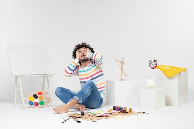 Vooraanzicht van een jonge man die rond verf en tekeningen op een witte muur zit
