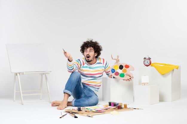 Vooraanzicht van een jonge man die verf en een kwast vasthoudt om op een witte muur te tekenen