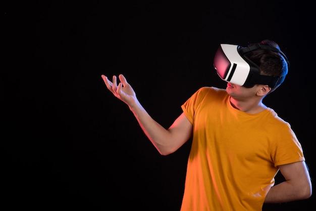 Vooraanzicht van een jonge man die virtual reality speelt op de donkere muur