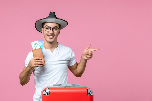 Vooraanzicht van een jonge man die vliegtickets vasthoudt en op vakantie gaat op de roze muur