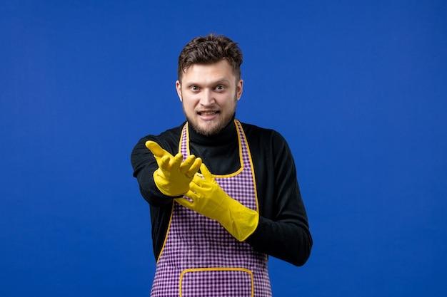 Vooraanzicht van een jonge man die zijn hand uitstrekt en op een blauwe muur staat