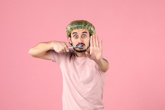 Vooraanzicht van een jonge man die zijn tanden poetst op roze muur