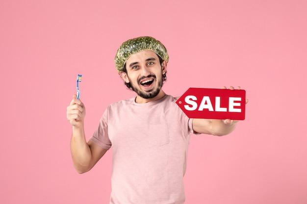 Vooraanzicht van een jonge man die zijn tanden schoonmaakt en een verkoopbanner op een roze muur houdt