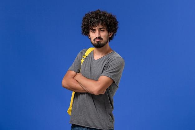 Vooraanzicht van een jonge man in een grijs t-shirt met een gele rugzak die net op de lichtblauwe muur poseren