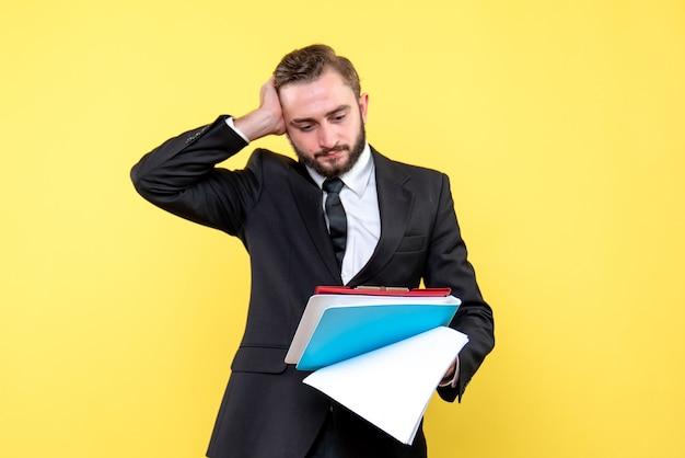 Vooraanzicht van een jonge man in zwart pak die zijn hand tegen zijn hoofd houdt en verward kijkt naar het rode klembord met de blauwe map op geel