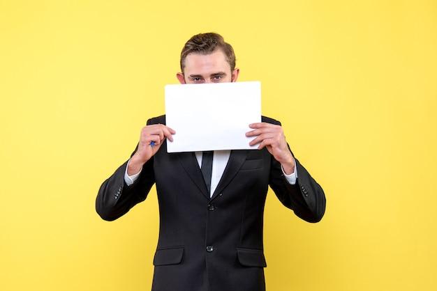 Vooraanzicht van een jonge man in zwart pak met een blanco wit papier met beide handen en het verbergen van een half gezicht op geel