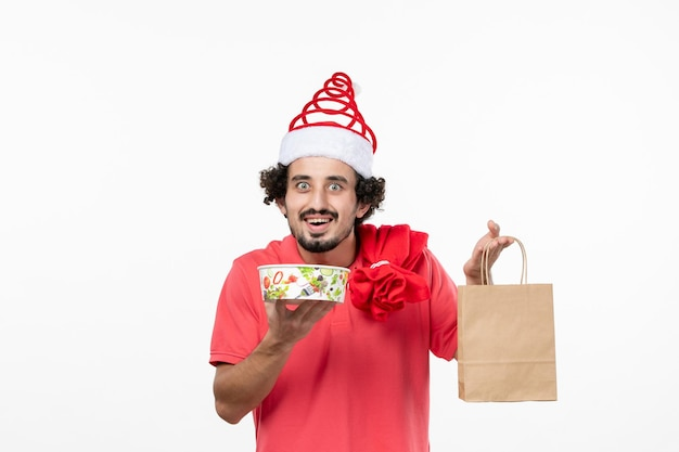 Vooraanzicht van een jonge man met bezorgmaaltijden op een witte muur