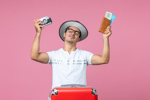 Vooraanzicht van een jonge man met camera en vliegtickets op de roze muur