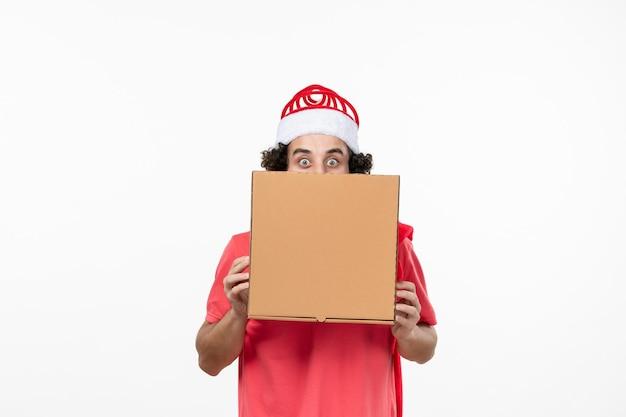 Vooraanzicht van een jonge man met een bezorgdoos op een witte muur