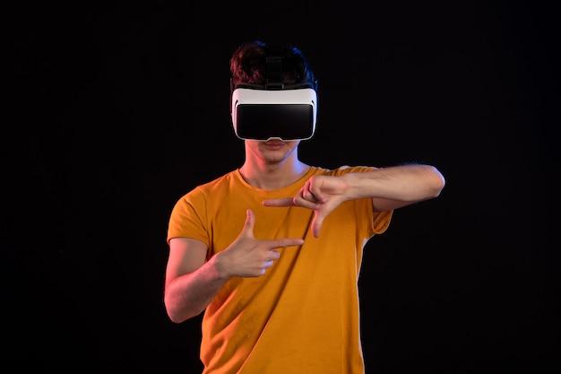 Vooraanzicht van een jonge man met een virtual reality-headset op een donkere muur