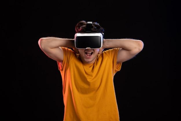 Vooraanzicht van een jonge man met een vr-headset op de donkere muur