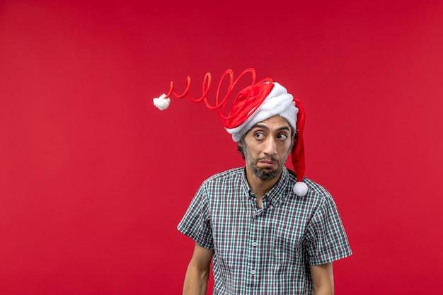 Vooraanzicht van een jonge man met grappige speelgoed pet op de rode muur