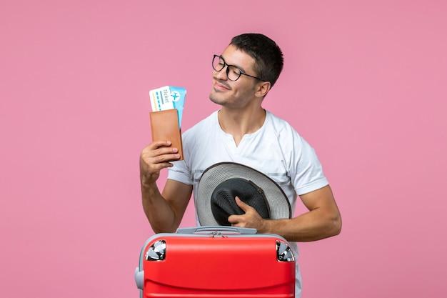 Vooraanzicht van een jonge man met vakantiekaartjes en zijn hoed op de roze muur