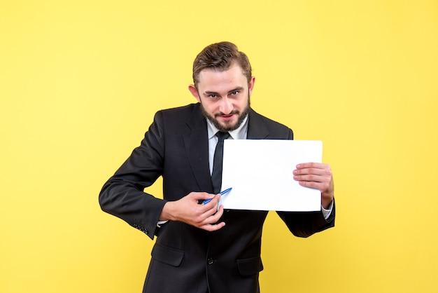 Vooraanzicht van een jonge man zakenman in een pak wijzend met een pen naar een blanco papier op geel