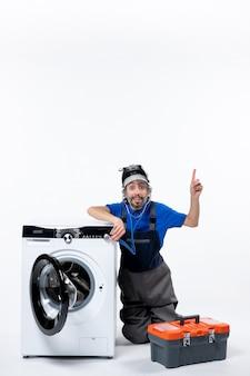 Vooraanzicht van een jonge reparateur die in de buurt van een wasmachine zit en zijn hand opsteekt op een witte geïsoleerde muur