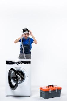 Vooraanzicht van een jonge reparateur in uniform die achter een wasmachine staat die de zak met pijpgereedschap op de muur blaast. op witte muur