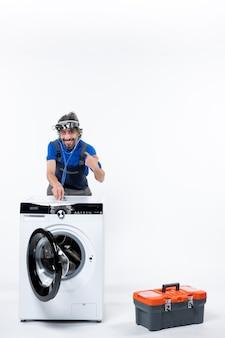 Vooraanzicht van een jonge reparateur met een koplamp die een stethoscoop op de wasmachine zet, wijzend naar zichzelf op een witte muur