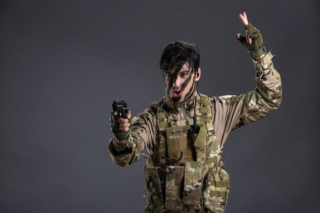 Vooraanzicht van een jonge soldaat in camouflage die een pistool op de donkere muur richt