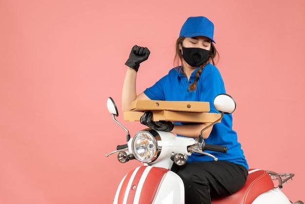 Vooraanzicht van een jonge, trotse vrouwelijke koerier met een medisch masker en handschoenen die op een scooter zitten en bestellingen afleveren op een pastelkleurige perzikachtergrond