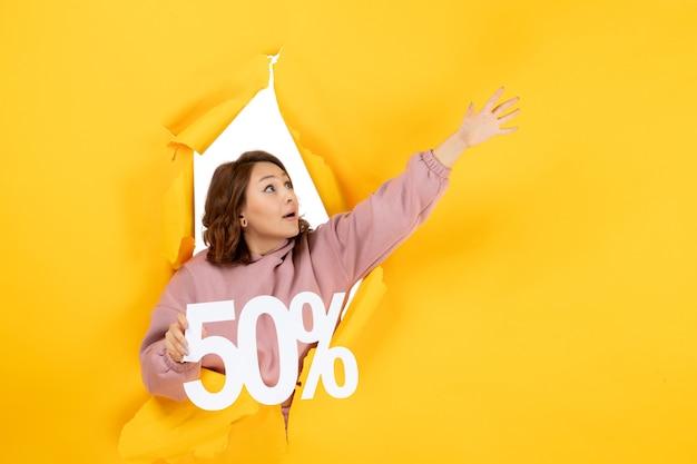 Vooraanzicht van een jonge verbaasde dame die een teken van vijftig procent toont en omhoog kijkt op gele torn