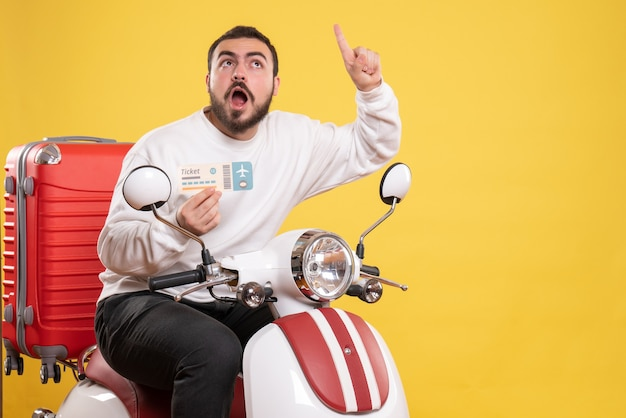 Vooraanzicht van een jonge, verraste reizende man die op een motorfiets zit met een koffer erop met een ticket naar boven gericht op een geïsoleerde gele achtergrond yellow