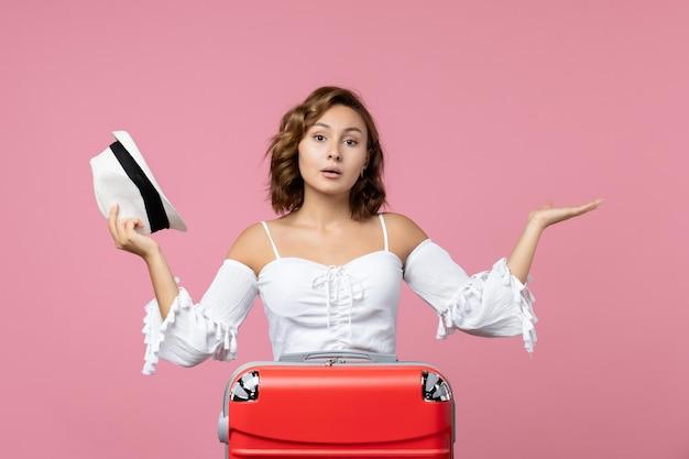 Vooraanzicht van een jonge vrouw die een hoed vasthoudt en zich voorbereidt op een reis met een rode tas op de roze muur