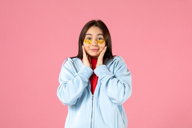 Vooraanzicht van een jonge vrouw die ooglapjes onder haar ogen op een roze muur zet
