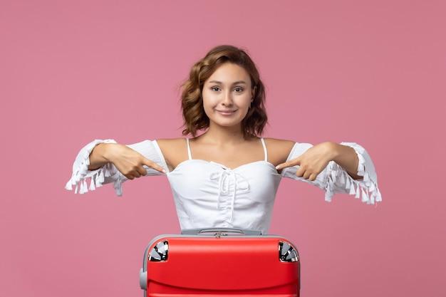 Vooraanzicht van een jonge vrouw die poseert met haar rode tas op de roze muur