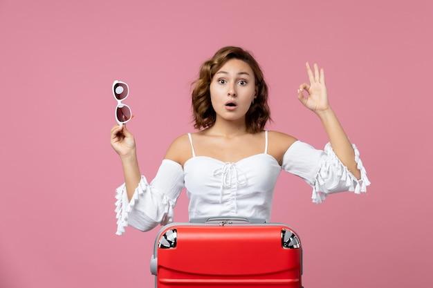 Vooraanzicht van een jonge vrouw die zich voordeed en zich voorbereidt op een reis met een rode tas op de roze muur