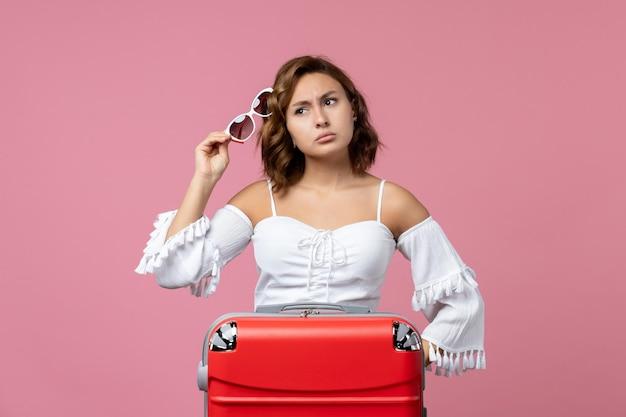 Vooraanzicht van een jonge vrouw die zich voordeed en zich voorbereidt op een reis met rode tas op roze vloer zeemodel vakantie kleur reisreis voyage
